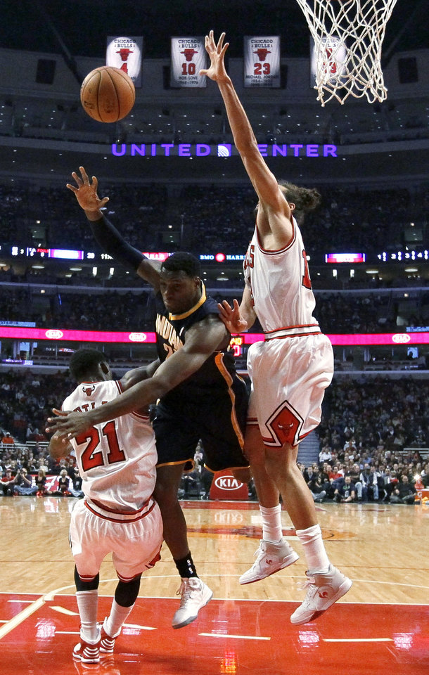 Indiana Pacers center Ian Mahinmi, center, throws up a shot between Chicago Bulls forward Jimmy Butler (21) and center Joakim Noah during the first half of an NBA basketball game Tuesday, Dec. 4, 2012, in Chicago. (AP Photo/Charles Rex Arbogast)