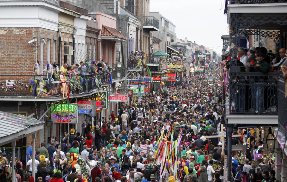 Photo - FILE - In this March 8, 2011 file photo, crowds throng Bourbon Street in the French Quarter on Mardi Gras day in New Orleans. New Orleans is perhaps best-known for hosting one of the biggest free parties in the world: Mardi Gras. The Carnival season includes parades with costumed riders, marching bands and decorated floats. (AP Photo/Gerald Herbert, file)