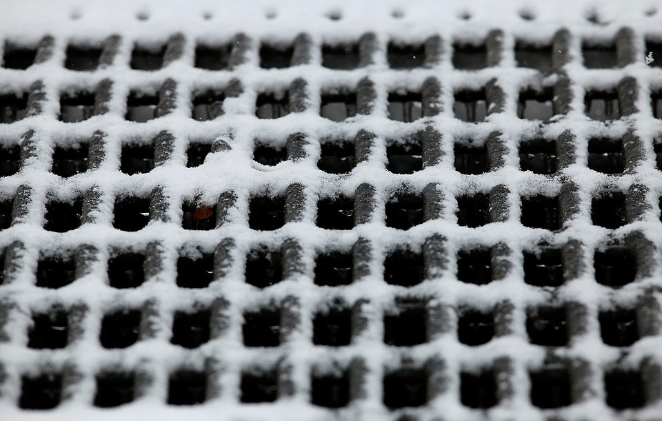 Photo - Snow and ice collect on a drainage grate Friday,  Jan. 29 , 2010. Photo by Jim Beckel, The Oklahoman