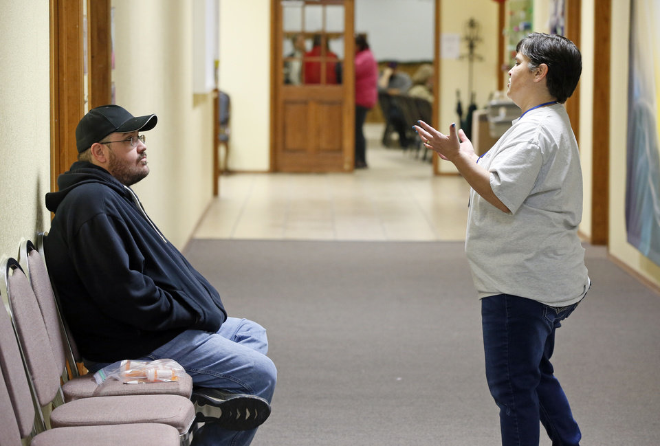 Photo -  Kyle Watts, of Moore, talks to volunteer Christina Holland, of Noble, while waiting to see a doctor during the Hope Medical Clinic at the Slaughterville Baptist Church. [PHOTO BY NATE BILLINGS, THE OKLAHOMAN]