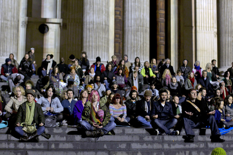 Supporters of the Occupy London Stock Exchange protest take part in a mass meditation on the steps of St Paul's Cathedral in London, Thursday, Oct. 27, 2011.  The senior St. Paul's Cathedral priest who welcomed anti-capitalist demonstrators to camp outside the London landmark resigned Thursday, saying he feared moves to evict the protesters could end in violence.  Other senior clergy and politicians urged the campers to leave peacefully, as the cathedral announced it would reopen to the public Friday after a weeklong closure triggered by the demonstrators' tents.  (AP photo/Matt Dunham) ORG XMIT: LMD121