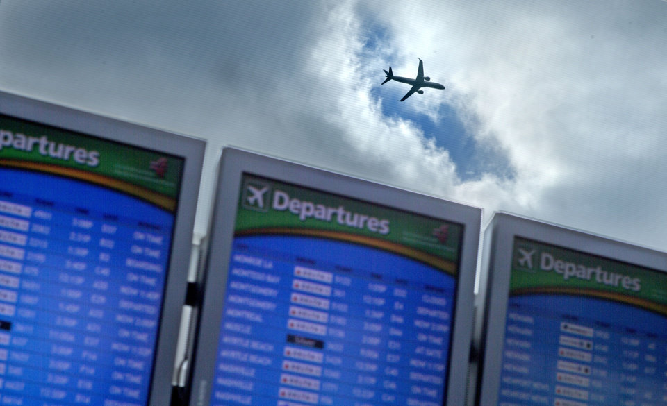 Photo - FILE - In this Wednesday, Nov. 27, 2013, file photo, a plane takes off over a departure board at Hartsfield-Jackson Airport, in Atlanta. Airfare has risen nearly 12 percent since the recessionary low in 2009, when adjusted for inflation, according to an Associated Press analysis of fare data from the Airlines Reporting Corp., which processes ticket transactions for airlines and more than 9,400 travel agencies, including online sites like Expedia and Orbitz. (AP Photo/David Goldman, File)
