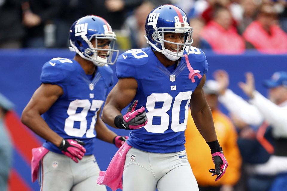 New York Giants wide receiver Victor Cruz (80) celebrates with teammate Domenik Hixon (87) after catching his third touchdown pass of the game during the second half of an NFL football game against the Cleveland Browns Sunday, Oct. 7, 2012, in East Rutherford, N.J. (AP Photo/Julio Cortez)