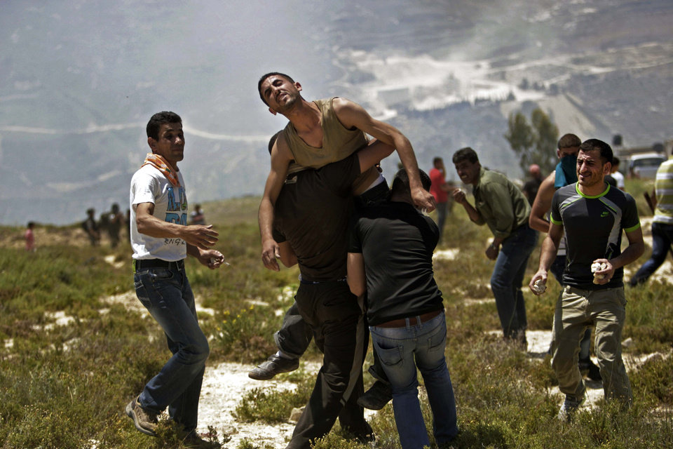 Photo - Palestinians help a wounded man during clashes with Jewish settlers near the Jewish settlement of Yitzhar, near Nablus, Tuesday, April 30, 2013. In the West Bank, a Palestinian man fatally stabbed an Israeli waiting at a bus stop and fired on police before he was detained by Israeli security forces, officials said. (AP Photo/Nasser Ishtayeh)