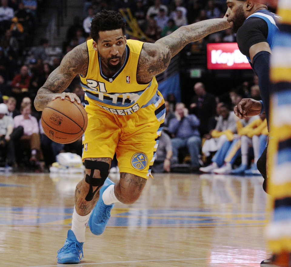 Photo - Denver Nuggets forward Wilson Chandler (21) drives past Dallas Mavericks guard Vince Carter  in the third quarter of an NBA game in Denver on Wednesday, March 5, 2014. Chandler had 21 points in Denver's 115-110 victory.(AP Photo/Joe Mahoney)