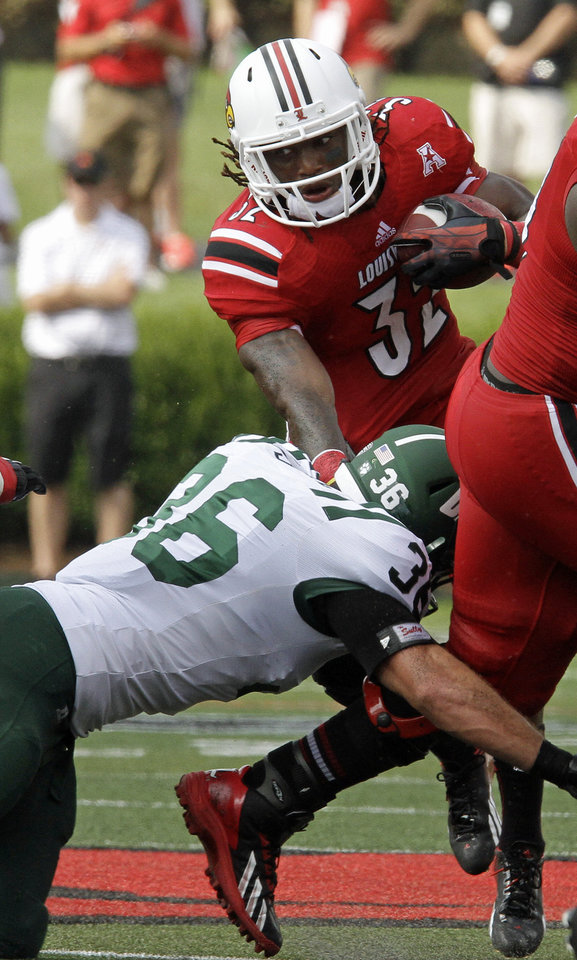 Photo - Louisville running back Senorise Perry (32) gets cut down by Ohio University linebacker Ben Russell (32) on this run in the second quarter of an NCAA college football game in Louisville, Ky., Sunday, Sept. 1, 2013. (AP Photo/Garry Jones)