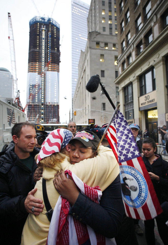 Photo - Dionne Layne, facing camera, hugs Mary Power as they react to the news of the death of Osama bin Laden, Monday, May 2, 2011 in New York. At left is the under construction 1 World Trade Center, also known as the Freedom Tower. (AP Photo/Mark Lennihan)