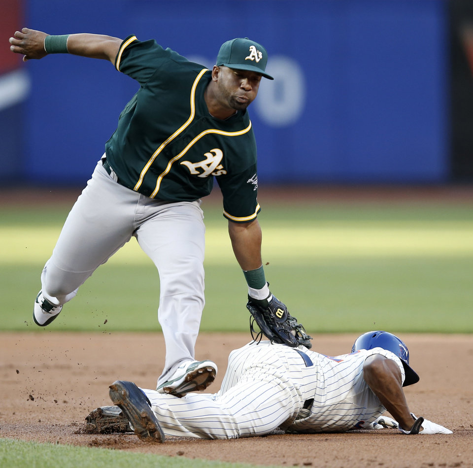 Photo - Oakland Athletics second baseman Alberto Callaspo catches New York Mets' Eric Young Jr. stealing in the first inning of an interleague baseball game in New York, Tuesday, June 24, 2014. (AP Photo/Kathy Willens)