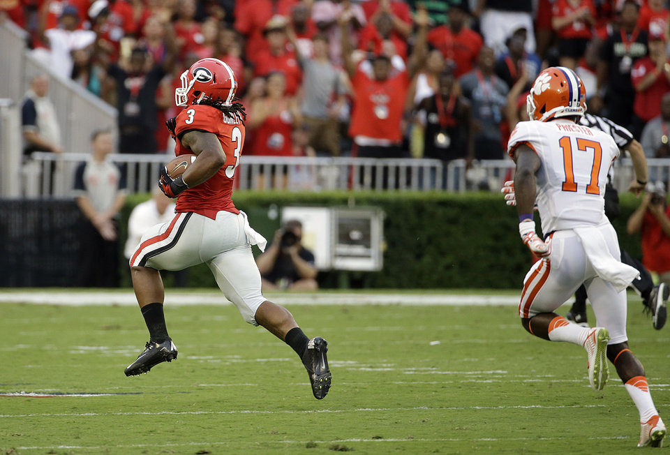 Photo - Georgia's Todd Gurley, left, breaks away from Clemson's Kyrin Priester to return a kick-off for a touchdown in the first half of an NCAA college football game, Saturday, Aug. 30, 2014, in Athens, Ga. (AP Photo/David Goldman)