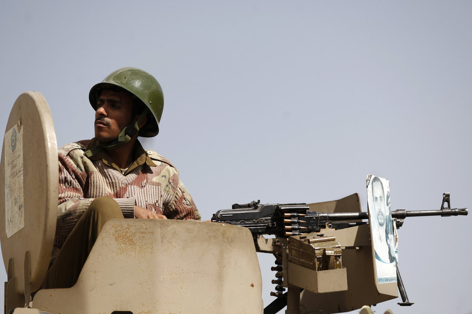 A Yemeni soldier sits atop a military vehicle securing a street during a rally by pro-democracy protestors in Sanaa, Yemen, Friday, Dec. 28, 2012. (AP Photo/Hani Mohammed)