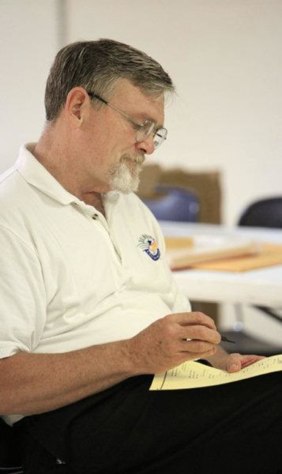 Photo -  John Richard uses a chair rather than a voting booth while marking his ballot at precinct 574, Sooner and Hefner roads, in northeast Oklahoma City Tuesday   PAUL B. SOUTHERLAND - PAUL B. SOUTHERLAND