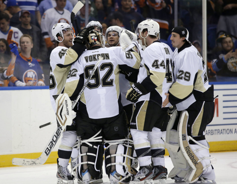 Photo - Pittsburgh Penguins, including defenseman Brooks Orpik (44), celebrate with goalie Tomas Vokoun (92), of the Czech Republic, after Orpik scored in overtime of Game 6 of the team's first-round NHL Stanley Cup playoff hockey series against the New York Islanders in Uniondale, N.Y., Saturday, May 11, 2013. The Penguins won 4-3, and advanced to the Eastern Conference semifinals. (AP Photo/Kathy Willens)