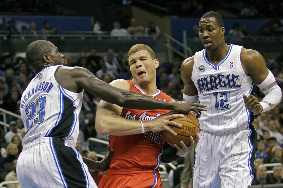Los Angeles Clippers' Blake Griffin, center, tries to get off a shot between Orlando Magic's Jason Richardson (23) and Dwight Howard (12) during the first half of an NBA basketball game in Orlando, Fla., Tuesday, Feb. 8, 2011.(AP Photo/John Raoux)