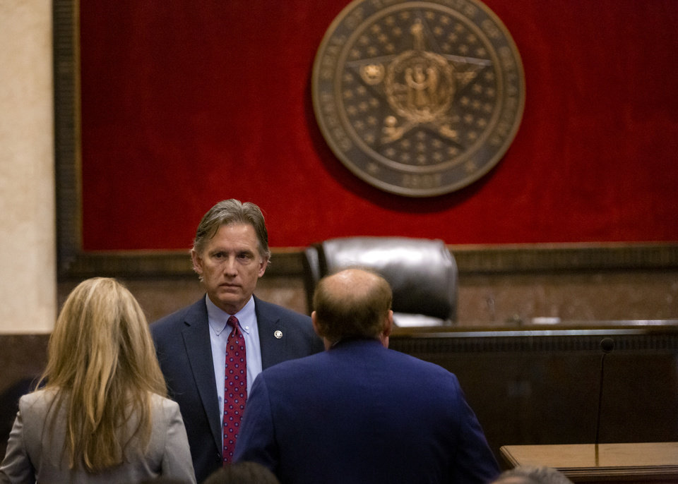 Photo - Attorney General Mike Hunter speaks to his attorneys before the start of the opioid trial at the Cleveland County Courthouse in Norman, Okla. on Wednesday, May 29, 2019. The proceeding are the first public trial to emerge from roughly 2,000 U.S. lawsuits aimed at holding drug companies accountable for the nationÕs opioid crisis.  [Chris Landsberger/The Oklahoman]