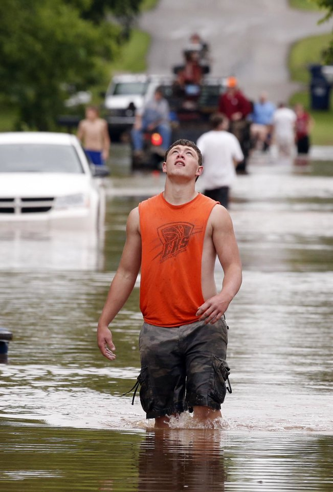 Photo - Fischer Bowling wades across a downtown street after checking on a friends house on the other side of the city divided by Saturday night's storms on Sunday, May 24, 2015 in Lexington Okla.  Photo by Steve Sisney The Oklahoman