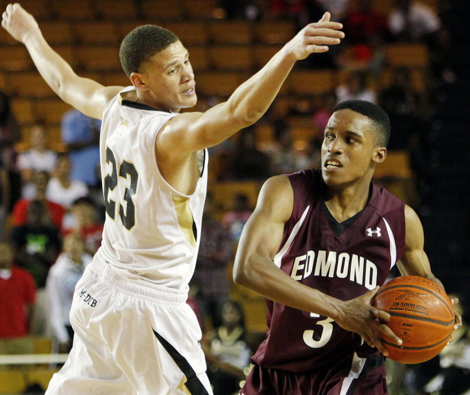 Photo - Edmond Memorial's James Woodard, right, keeps the ball away from Midwest City's Greg Austin during the 2011 Class 6A state championship game. Woodard and the Bulldogs advanced to the title game again in 2012 but lost to Tulsa Union. Photo by Nate Billings, The Oklahoman Archive