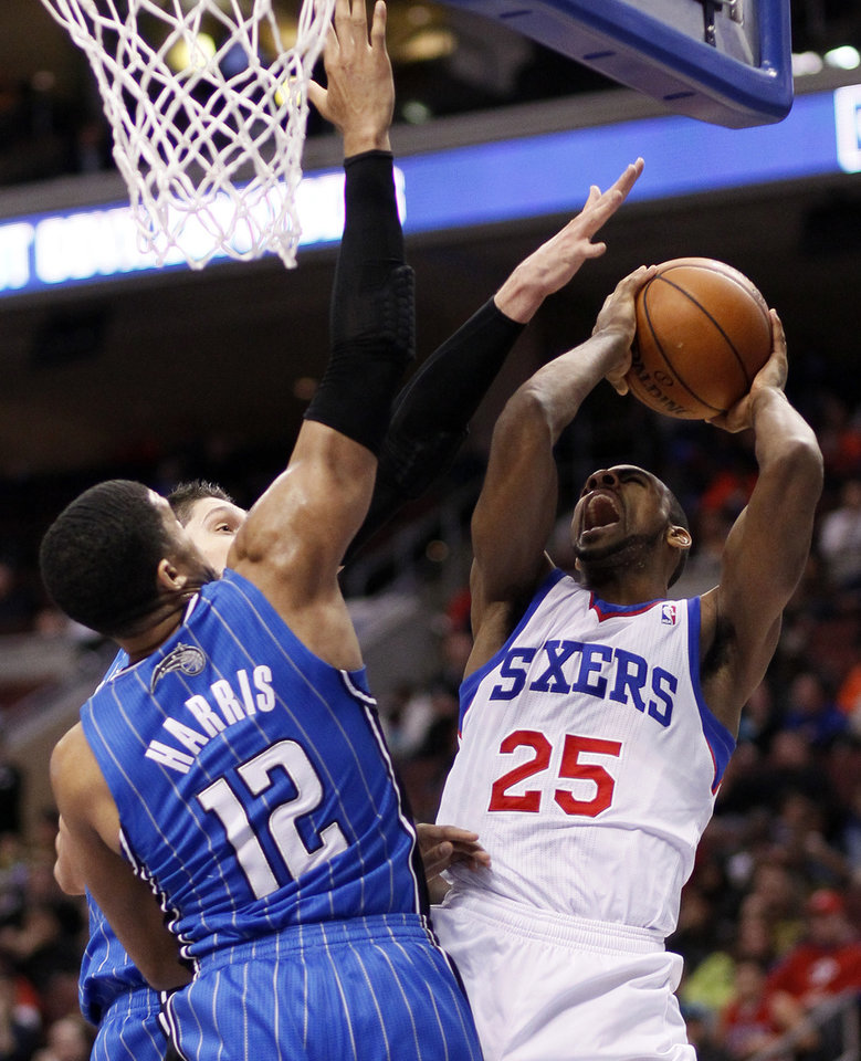 Photo - Philadelphia 76ers' Elliot Williams, right, finds his way to the hoop defended by Orlando Magic's Tobias Harris during the second half of an NBA basketball game, on Wednesday, Feb 26, 2014, in Philadelphia. (AP Photo/Tom Mihalek)