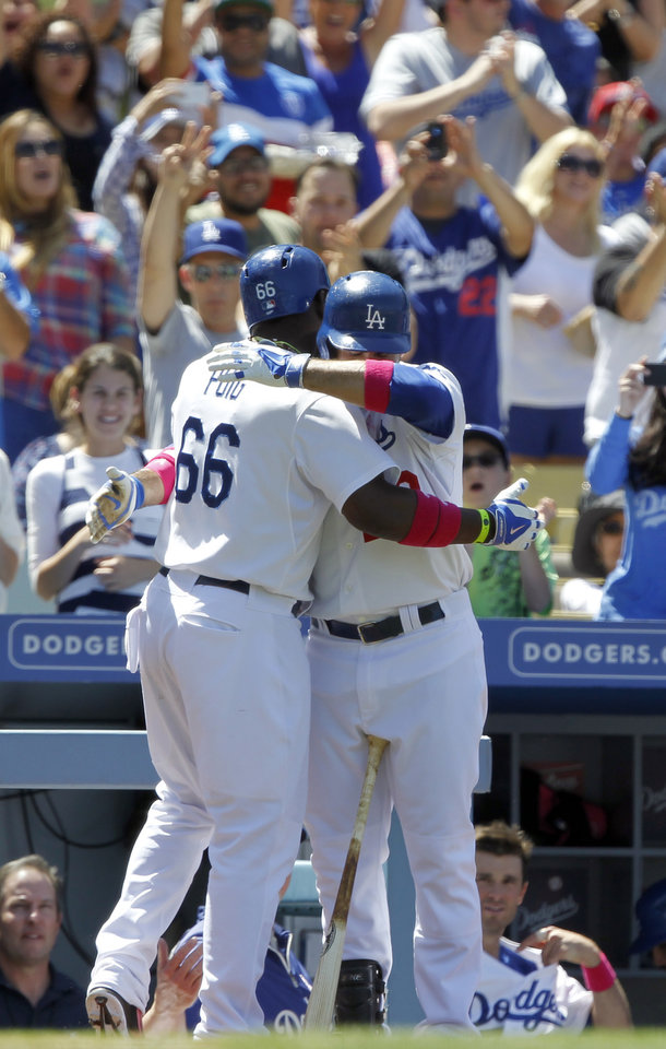 Photo - Los Angeles Dodgers' Yasiel Puig (66) gets a hug from Adrian Gonzalez after Puig hit a solo home run against the San Francisco Giants in the sixth inning of a baseball game on Sunday, May 11, 2014, in Los Angeles. (AP Photo/Alex Gallardo)