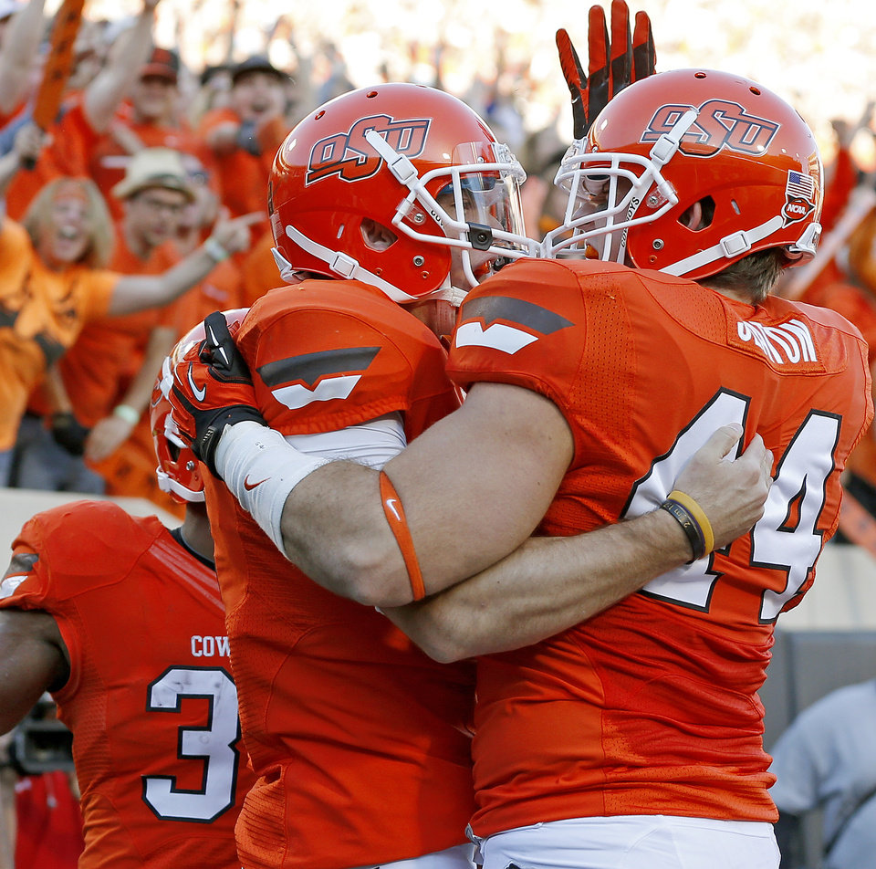 Oklahoma State\'s J.W. Walsh (4) celebrates with Jeremy Seaton (44) after a touchdown during a college football game between Oklahoma State University (OSU) and Texas Tech University (TTU) at Boone Pickens Stadium in Stillwater, Okla., Saturday, Nov. 17, 2012. Photo by Bryan Terry, The Oklahoman