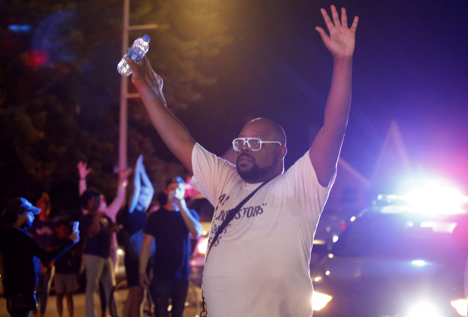 Photo - A protester hold his hands in the air on  Pennsylvania Avenue during a protest near the intersection of 23rd and Classen in Oklahoma City, Saturday, May 30, 2020. The protest was in response to the death of George Floyd. [Sarah Phipps/The Oklahoman]