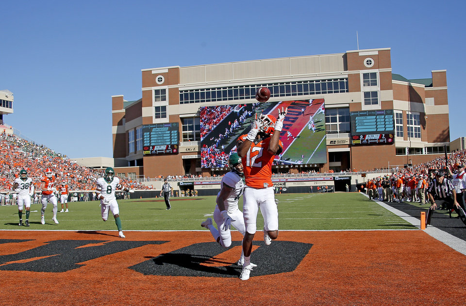 Photo - Oklahoma State's Jordan McCray (12) catches a touchdown as Baylor's Raleigh Texada (13) defends in the first quarterduring the college football game between Oklahoma State University and Baylor at Boone Pickens Stadium in Stillwater, Okla., Saturday, Oct. 19, 2019. [Sarah Phipps/The Oklahoman]