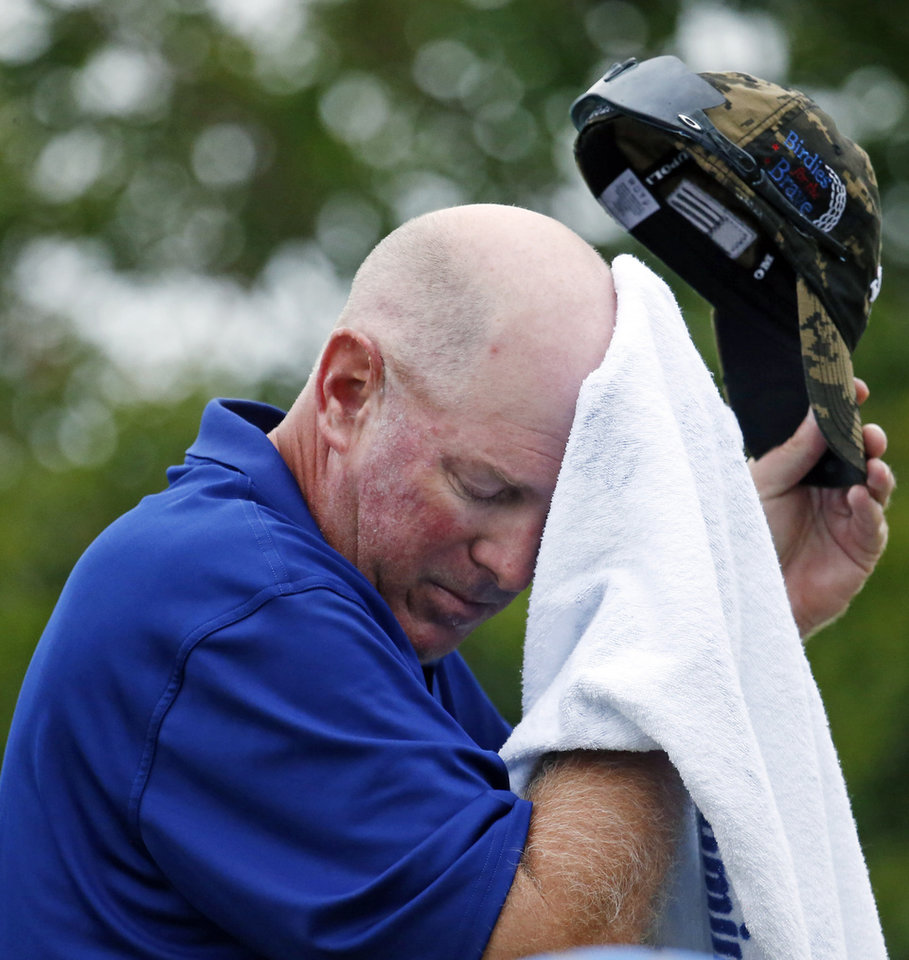 Photo - Frank Lickliter II wipeS away sweat on the first hole of the first round of the Sanderson Farms Championship golf tournament, Thursday, July 18, 2013 in Madison, Miss. (AP Photo/Rogelio V. Solis)