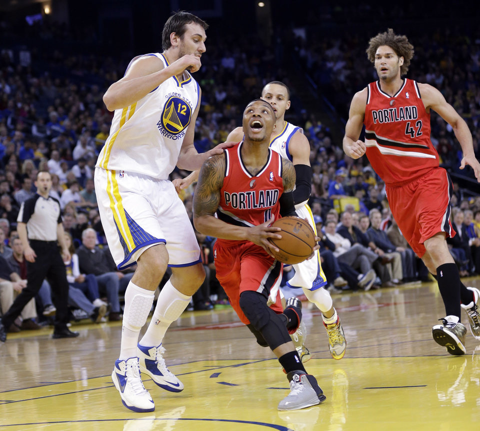 Photo - Portland Trail Blazers' Damian Lillard (0) drives to the basket as Golden State Warriors' Andrew Bogut (12) defends during the first half of an NBA basketball game on Sunday, Jan. 26, 2014, in Oakland, Calif. (AP Photo/Marcio Jose Sanchez)