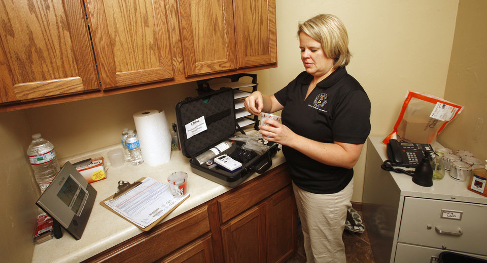 Photo - Susan Lobsinger, president of USA Mobile Drug Testing of Oklahoma, opens a testing kit cup Aug. 17 in the testing room at her office in Oklahoma City. Photos by Paul B. Southerland, The Oklahoman