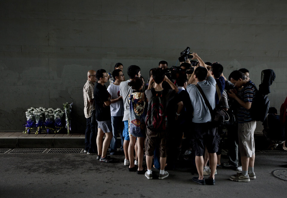 Photo -   Journalists and pedestrian surrounding a man who placed flowers under a railway bridge, where a motorist drowned a week ago in Beijing, China Saturday, July 28, 2012. A small group of people laid down white chrysanthemums or lit candles Saturday to pay tribute to those who died in the storm that ravaged Beijing one week ago, killing at least 77. (AP Photo/Andy Wong)