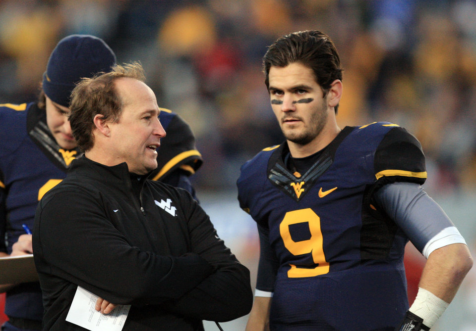 West Virginia coach Dana Holgorsen speaks with quarterback Clint Trickett (9) during a timeout in the second quarter of their NCAA college football game against Iowa State in Morgantown, W.Va., on Saturday, Nov. 30, 2013. (AP Photo/Christopher Jackson)