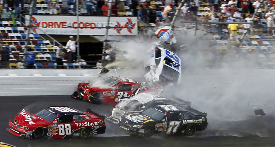Kyle Larson (32) goes into the catch fence as he collides with Justin Allgaier (31), Brian Scott (2), Parker Klingerman (77) and Dale Earnhardt Jr. (88) at the conclusion of the NASCAR Nationwide Series auto race Saturday, Feb. 23, 2013, at Daytona International Speedway in Daytona Beach, Fla. (AP Photo/Terry Renna)