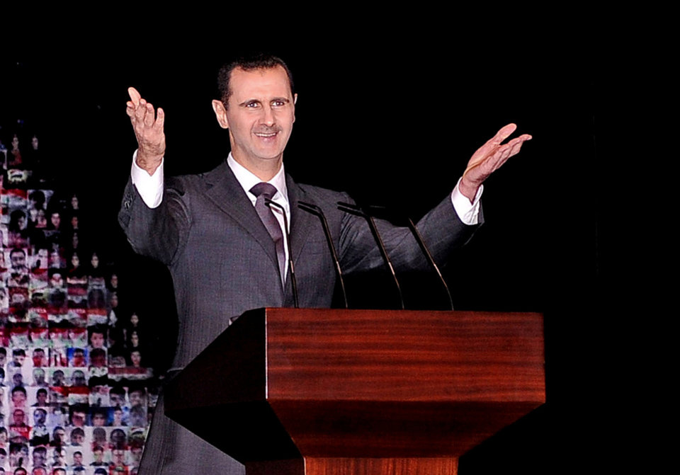 Photo - In this photo released by the Syrian official news agency SANA, Syrian President Bashar Assad gestures as speaks at the Opera House in central Damascus, Syria, Sunday, Jan. 6, 2013. Syrian President Bashar Assad on Sunday outlined a new peace initiative that includes a national reconciliation conference and a new government and constitution but demanded regional and Western countries stop funding and arming rebels first. (AP Photo/SANA)