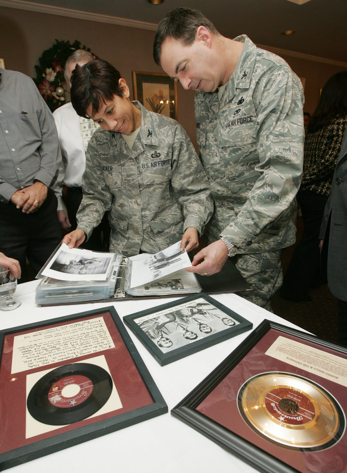 Photo - Col. Mona Lisa Tucker, the 72nd ABW vice commander and Col. James Eilers, 72nd Mission Support Group commander, look at Buddy Holly photos and a plaque that was re-dedicated at the officers club at Tinker Air Force Base in  Okla. December 05, 2008.  BY STEVE GOOCH, THE  OKLAHOMAN.  ORG XMIT: KOD