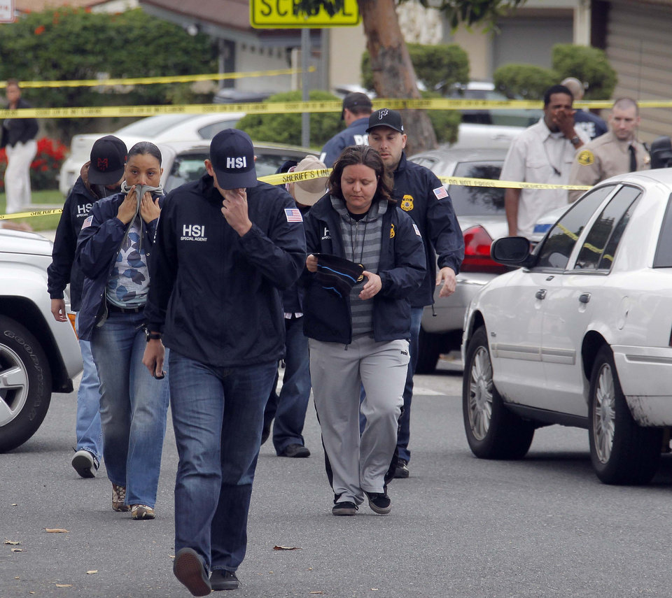 Photo -   U.S. Immigration and Customs Enforcement agents wait in the street for the coroner's van at the a home of an ICE agent who was shot in Carson, Calif. on Thursday, May 3, 2012. The 14-year-old son of the agent was arrested Thursday in the shooting death of his father in their Southern California home, authorities said. (AP Photo/Nick Ut)
