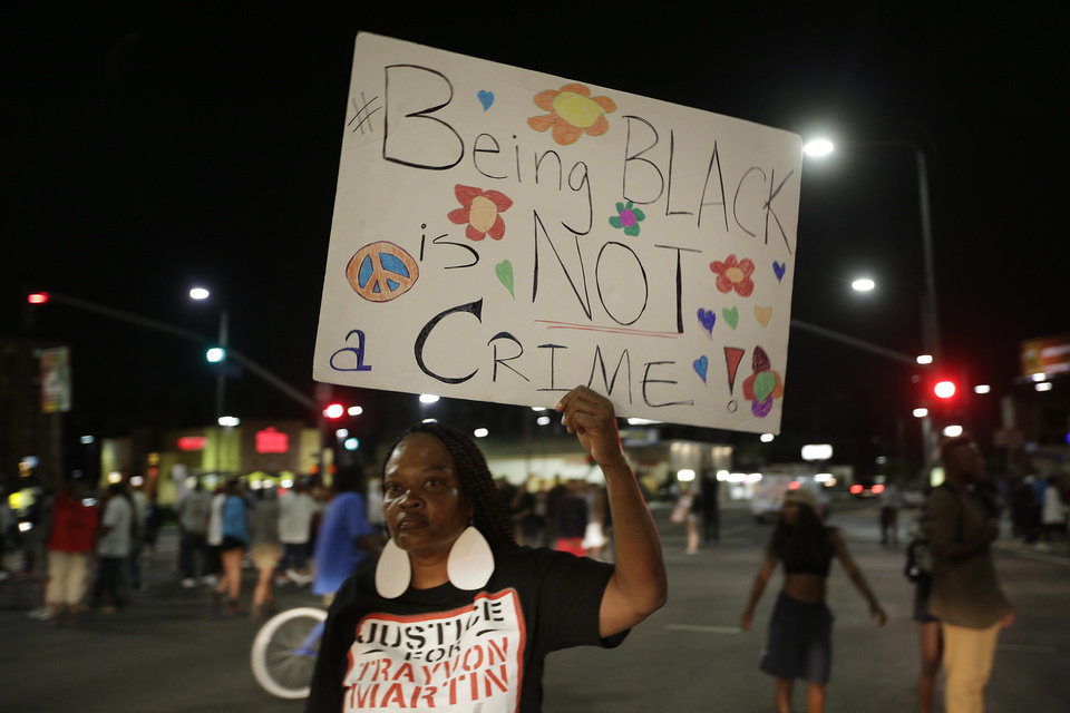 Photo - A woman holds up a sign during a demonstration in reaction to the acquittal of neighborhood watch volunteer George Zimmerman on Monday, July 15, 2013, in Los Angeles. Anger over the acquittal of a U.S. neighborhood watch volunteer who shot dead an unarmed black teenager continued Monday, with civil rights leaders saying mostly peaceful protests will continue this weekend with vigils in dozens of cities. (AP Photo/Jae C. Hong)