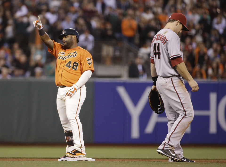 Photo - San Francisco Giants' Pablo Sandoval, left, reacts after hitting an RBI double off Arizona Diamondbacks starting pitcher Mike Bolsinger as Arizona first baseman Paul Goldschmidt, right, walks away in the fifth inning of a baseball game Friday, July 11, 2014, in San Francisco. Hunter Pence scored on the play. (AP Photo/Eric Risberg)