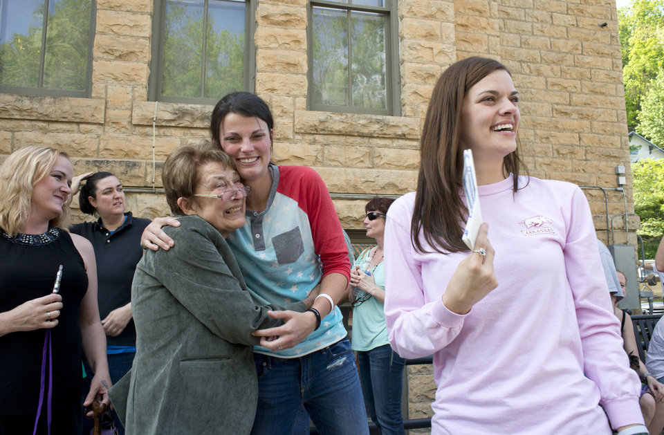 Photo - Jennifer Rambo, right, smiles as her partner Kristin Seaton, center, hugs Sheryl Maples, left, the lead attorney who filed the Wright v. the State of Arkansas lawsuit, Saturday, May 10, 2014, in Eureka Springs, Ark. A judge overturned amendment 83 Friday, which banned same-sex marriage in the state of Arkansas. (AP Photo/Sarah Bentham)