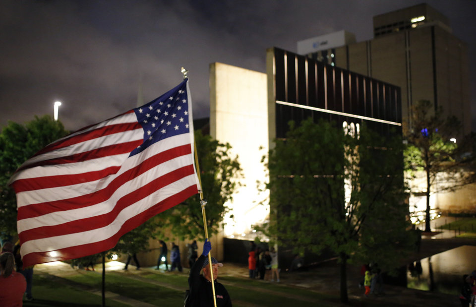 Photo - A man holds an American flag at the Survivor Tree during the Sunrise Service before the 2017 Oklahoma City Memorial Marathon Sunday, April 30, 2017.  Photo by Sarah Phipps, The Oklahoman