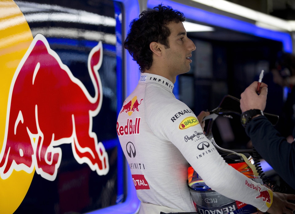Photo - Red Bull driver Daniel Ricciardo of Australia chats with his crew member at the garage during the practice session ahead of Sunday's Chinese Formula One Grand Prix at Shanghai International Circuit in Shanghai, China Friday, April 18, 2014. (AP Photo/Andy Wong)