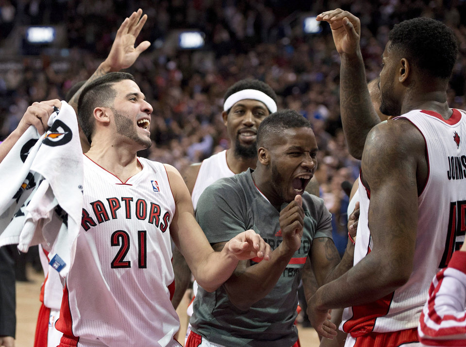 Photo - Toronto Raptors' Amir Johnson, right, who made the game winning shot, is congratulated by teammates Greivis Vasquez, left, and Dwight Buycks after defeating the Boston Celtics in NBA action in Toronto on Friday March 28, 2014. The Raptors clinched a playoff spot with the win. (AP Photo/The Canadian Press, Frank Gunn)