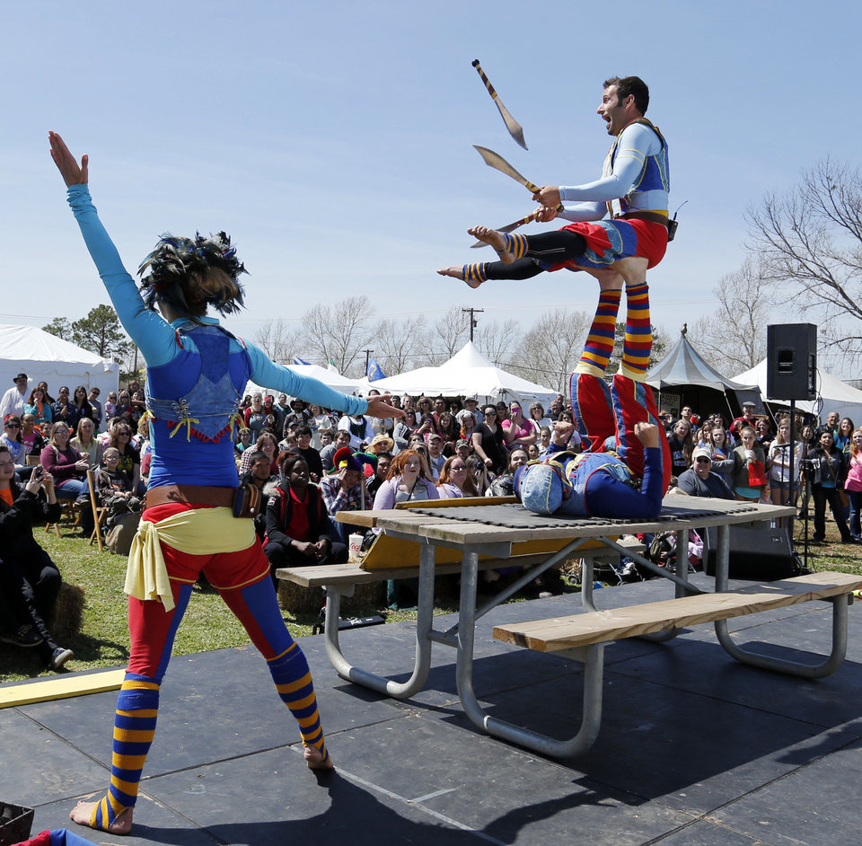 Cameron Tomele jugles perched atop James Freer\'s feet as Margaret Ebert frames the stage during a Friday performance by Barely Balanced during the Medieval Fair in Norman. Photo by Steve Sisney, The Oklahoman STEVE SISNEY
