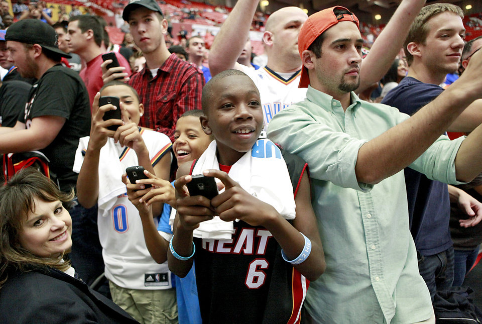 Photo - J.D. Sims (center) of Lawton, Gaylan Towle (right), of Edmond, and other fans watch Kevin Durant walk onto the court during the US Fleet Tracking Basketball Invitational at the Cox Convention Center in Oklahoma City Sunday, Oct. 23, 2011. Photo by John Clanton, The Oklahoman