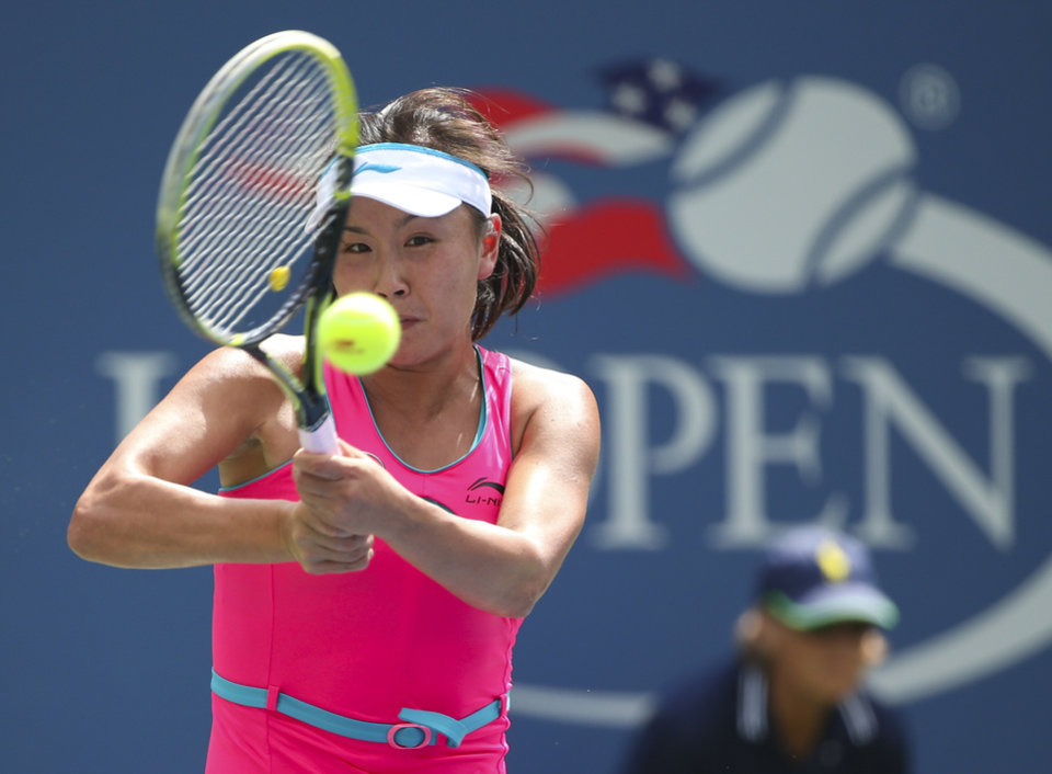 Photo - Peng Shuai, of China, returns a shot against Belinda Bencic, of Switzerland, during the quarterfinals of the 2014 U.S. Open tennis tournament, Tuesday, Sept. 2, 2014, in New York. (AP Photo/Mike Groll)