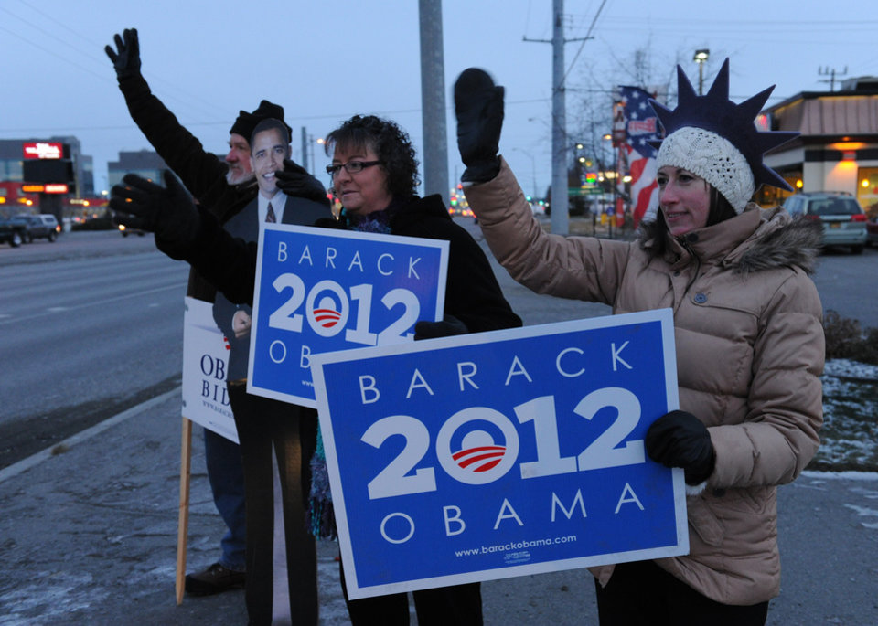 John Hoffman, with a card board President Obama, Cindy Emery and Sarah Robinson wave signs in support of the President early on Election Day at the corner of the Seward Highway and Benson Boulevard in Anchorage on Tuesday, Nov. 6, 2012. (AP Photo/Anchorage Daily News, Bob Hallinen)