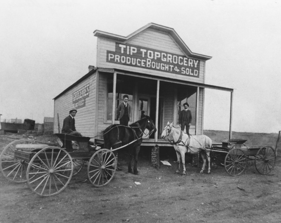 "HISTORIC EARLY DAYS / OKLAHOMA CITY, OK / GROCERY STORES:  Proprietors of the Tip Top Grocery had the foresight to anticipate the suburbs of Oklahoma City.  In this 1904 photo the store was on a country road at what is now NW 10 and Western.  In the wagon is Frank Young; at left on the porch is owner J.S. Kiker. At right is Ben Secor.  Published on 04/16/1989 in The Daily Oklahoman in the Special Centennial supplement ""Growth"" section.  Original photo arrived in library on 10/20/1961"