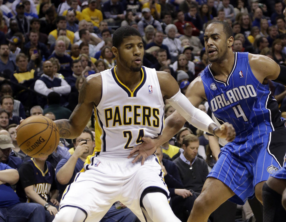Photo - Indiana Pacers forward Paul George, left, gets past Orlando Magic guard Arron Afflalo as he drives the baseline in the second half of an NBA basketball game in Indianapolis, Monday, Feb. 3, 2014. The Pacers defeated the Magic 98-79. (AP Photo/Michael Conroy)