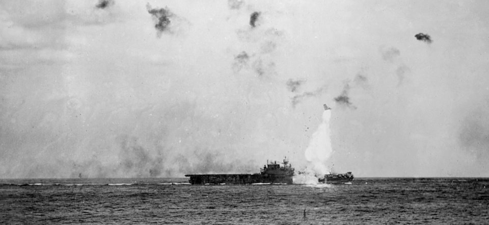 Photo -  The forward elevator blasts into the sky after the USS Enterprise was struck by a kamikaze attack in May 1945. Roy Wright, 91, of northwest Oklahoma City, was on deck when a Japanese Zero struck the aircraft carrier. [National Archives photo]