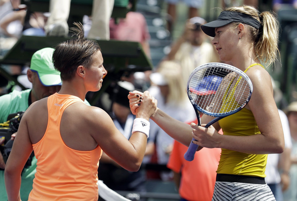 Photo - Maria Sharapova, of Russia, right, shakes hands with Kirsten Flipkens, of Belgium, after winning 3-6, 6-4, 6-1 at the Sony Open tennis tournament, Monday, March 24, 2014, in Key Biscayne, Fla. (AP Photo/Lynne Sladky)