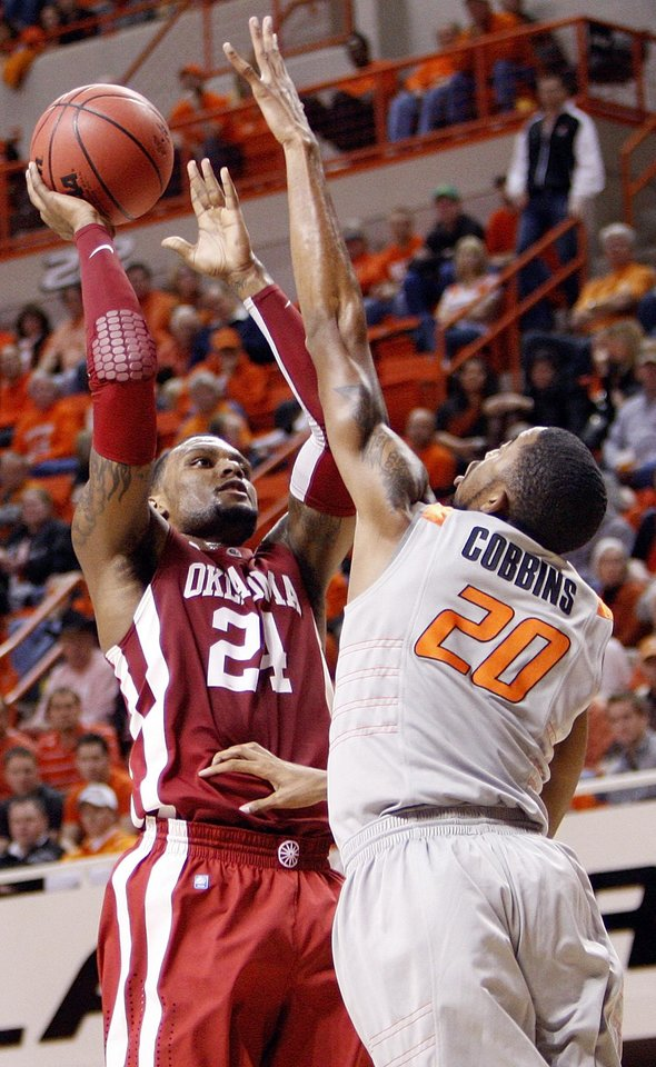 Photo - OU's Romero Osby (24) shoots over Michael Cobbins (20) of OSU in the first half during the Bedlam men's college basketball game between the Oklahoma State University Cowboys and the University of Oklahoma Sooners at Gallagher-Iba Arena in Stillwater, Okla., Monday, Jan. 9, 2012. Photo by Nate Billings, The Oklahoman