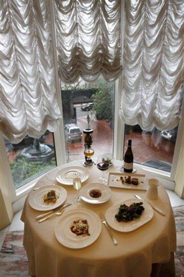 In this Dec. 7, 2012 photo, the reveillon menu of executive chef Kristin Butterworth, is seen with wine pairings and cafe brulot in a tea siphon, center rear, at the Grill Room of the Windsor Court Hotel on a rainy day in old New Orleans. Roughly 50 restaurants in New Orleans are reviving an old Creole custom called reveillon, which stems from the old French tradition of eating a lavish meal after midnight Mass on Christmas Eve. (AP Photo/Gerald Herbert)